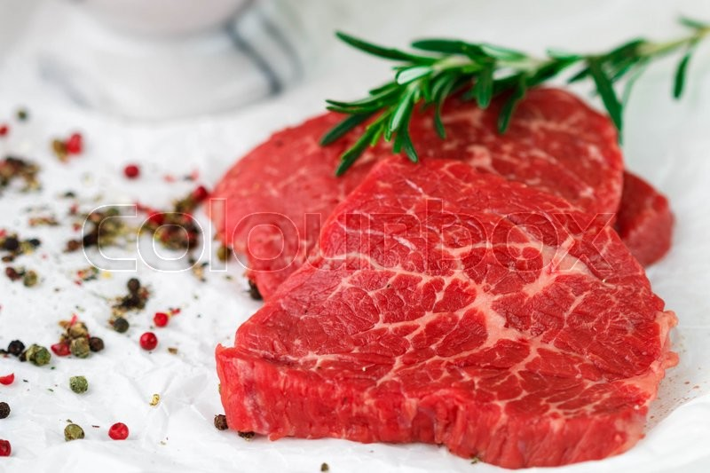 Stock image of 'Raw fresh steaks from the marble beef, rosemary and spices on the table. Selective focus'