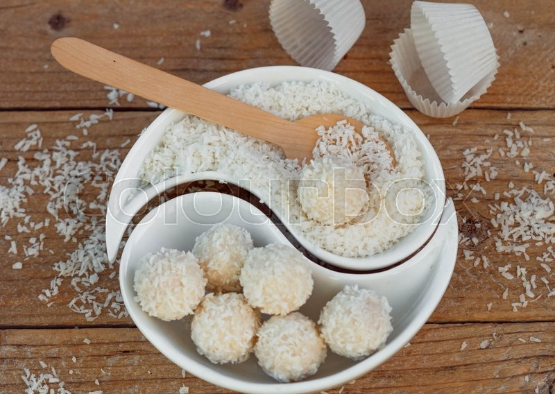 Stock image of 'Making truffles white chocolate with coconut. Homemade candy. Rustic style'