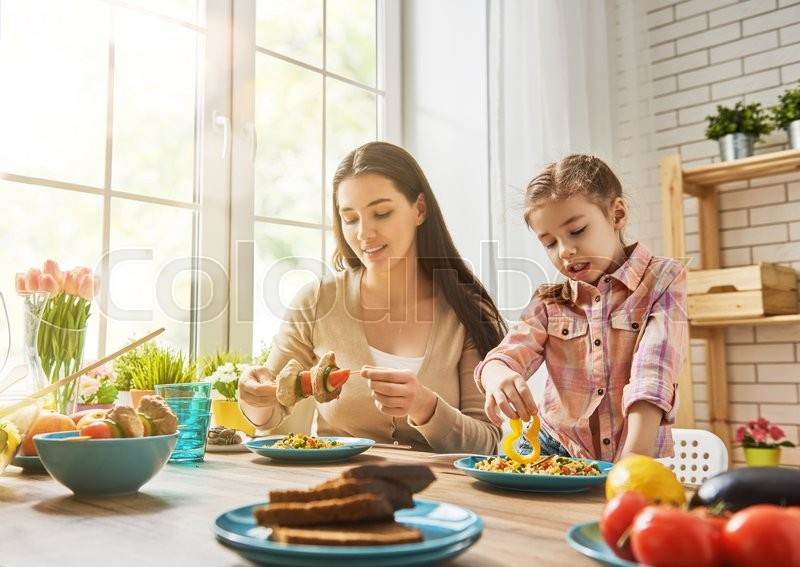 Stock image of 'Happy family having dinner together sitting at the rustic wooden table. Mother and her daughter enjoying family dinner together.'