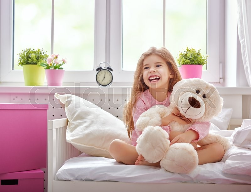 Stock image of 'The child girl woke up and enjoys the morning sun. Girl laugh and hugs the teddy bear.'