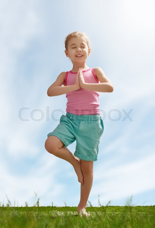 Stock image of 'child practicing yoga on the grass outdoors'