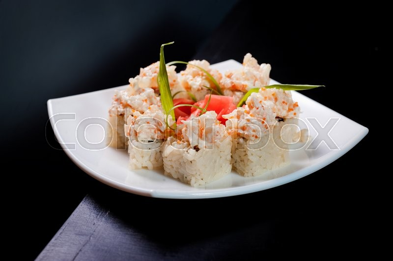 Stock image of 'Set of rolls on a white plate on a wooden dark table.'