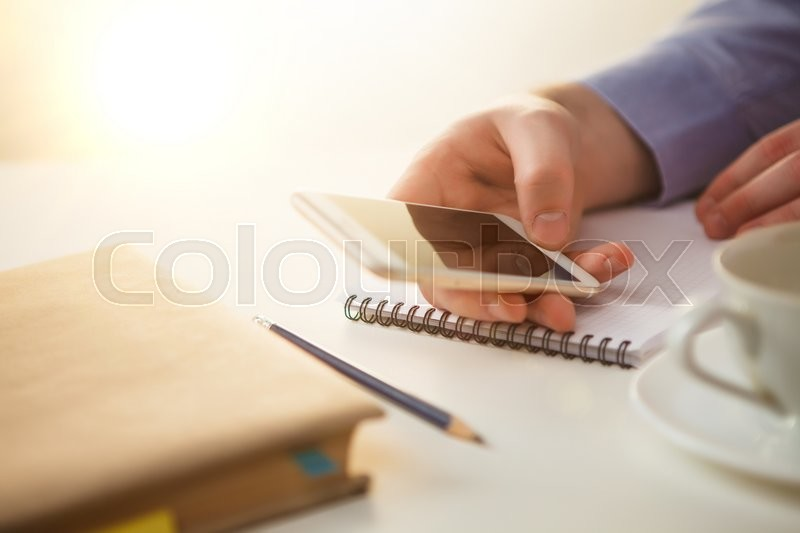Stock image of 'The male hand holding a phone against the background of the table'