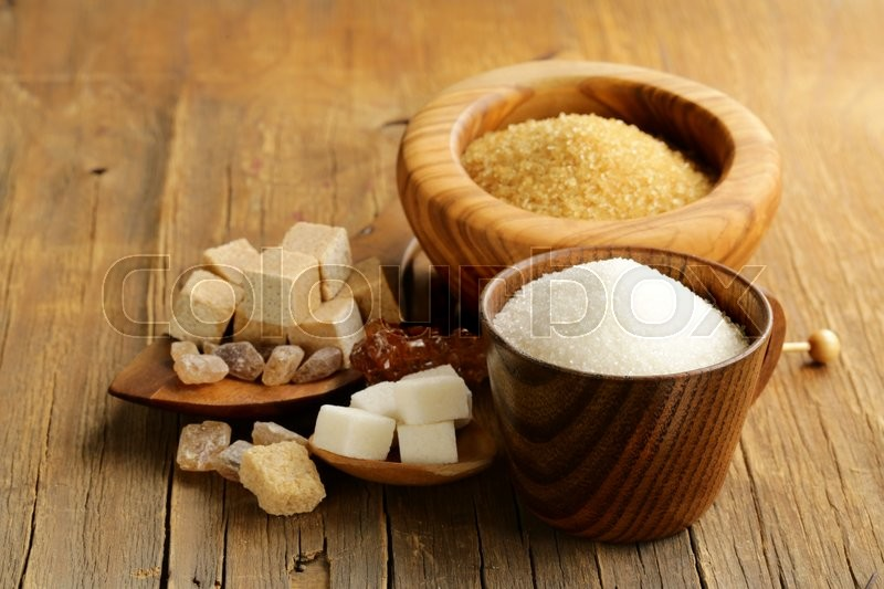 Stock image of 'different kinds of sugar - brown, white, refined sugar on a wooden background'
