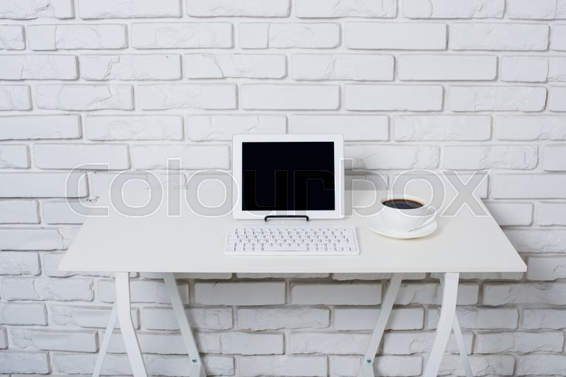 Stock image of 'Minimalistic white workspace, office table with laptop near white brick wall.'