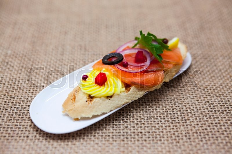 Stock image of 'Fresh Spanish tapas on bread baguette smoked Norwegian salmon with black olive butter, herbs and onions. An excellent background for the menus, the restaurant, the Cafe Mediterranean cuisine.'