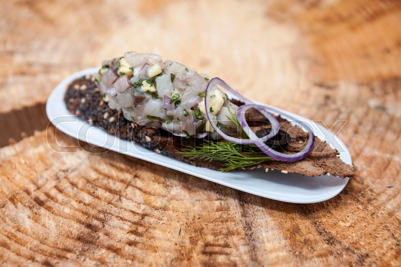 Stock image of 'Fresh, delicious Spanish tapas with Tartar of herring and onions on a black baguette. An excellent background for the menus, cafe, restaurant.'