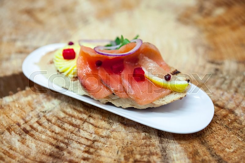 Stock image of 'Fresh Spanish tapas on bread baguette smoked Norwegian salmon with black olive butter, herbs and onions. An excellent wood background for the menus, the restaurant, the Cafe Mediterranean cuisine.'