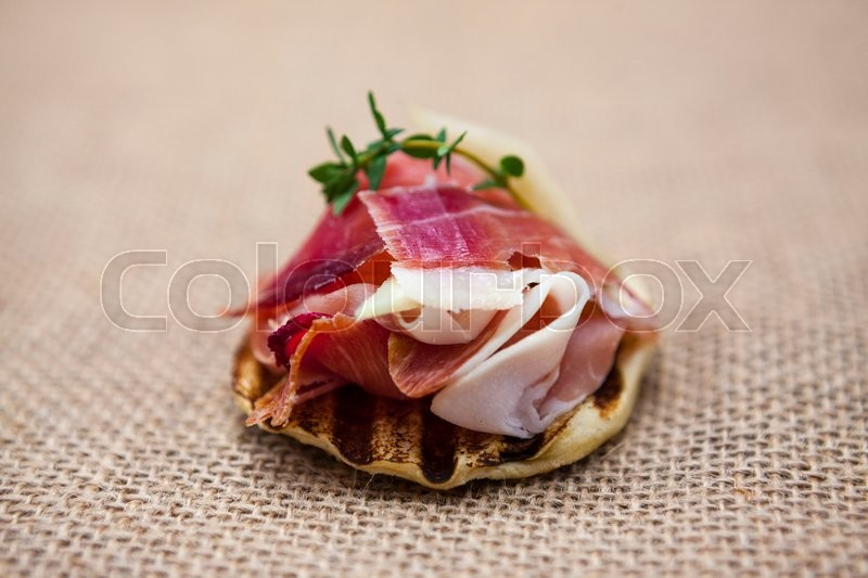 Stock image of 'Fresh delicious Spanish tapas with hamon with fresh herbs and strawberries on the  texture background . Great background for restaurant, cafe.'