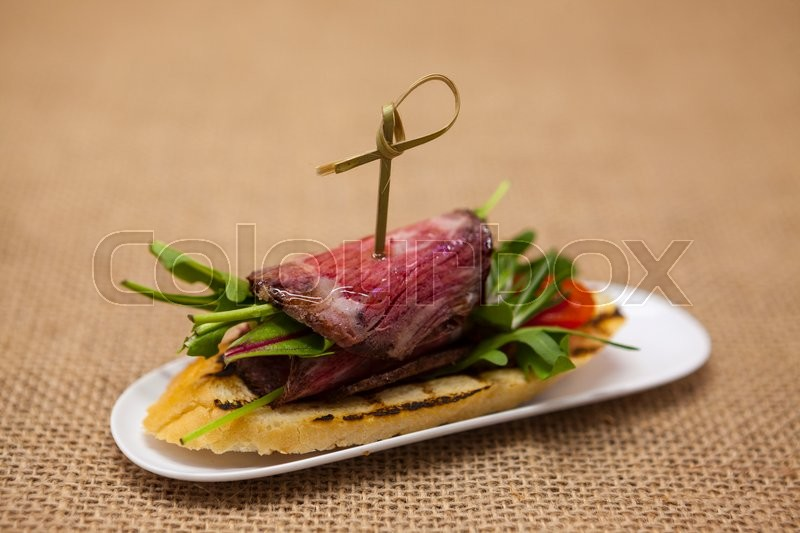 Stock image of 'Fresh delicious Spanish tapas with  roast beef  on the textiles background . Great background for restaurant, cafe.'