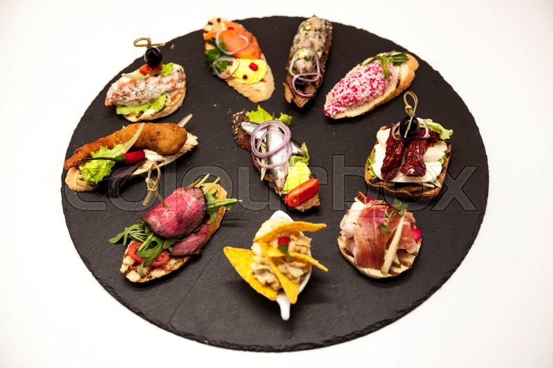 Stock image of 'Set of Spanish tapas on the stone plate on a white background. Great background for restaurant, cafe.'