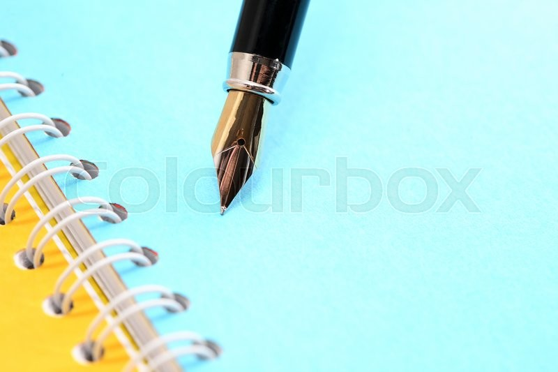 Stock image of 'Stationery background. Fountain pen on notebook with colored blank pages'