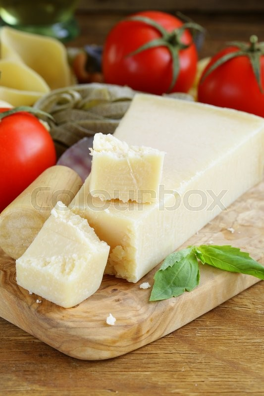 Stock image of 'piece of natural parmesan cheese on a wooden board'