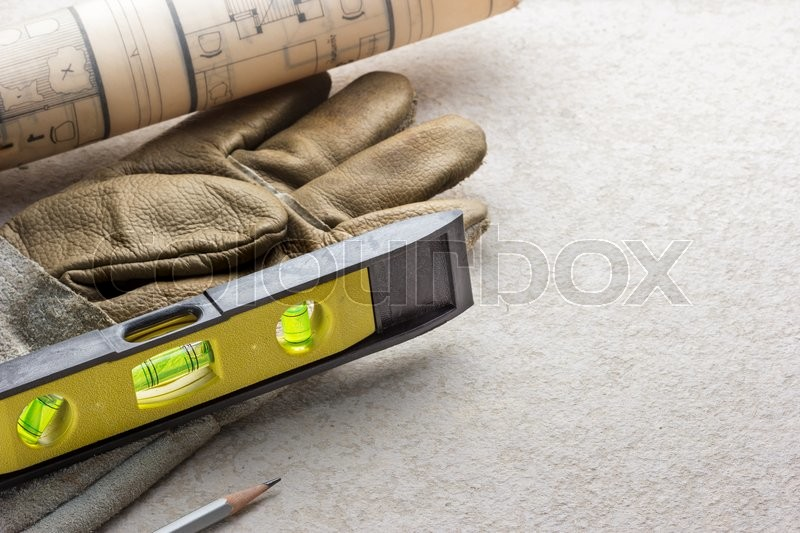 Stock image of 'Building level with glove and tool on cement background.'