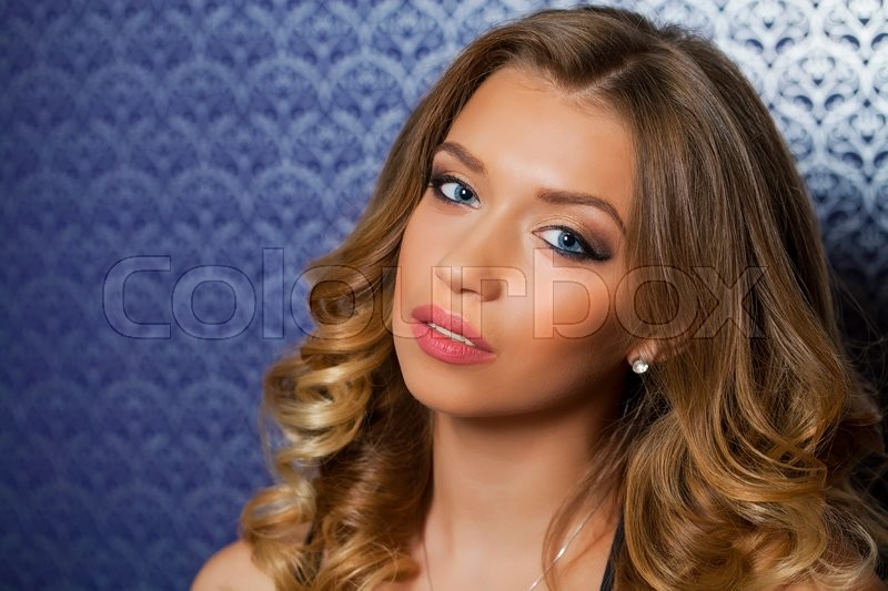 Stock image of 'Beauty portrait of young curly blonde woman, isolated on dark background'