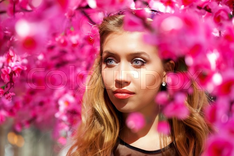 Stock image of 'Close up portrait of a beautiful young blonde woman on the background of the cherry blossoms, spring park'