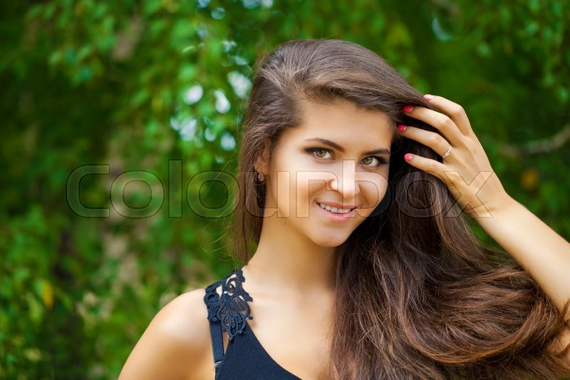 Stock image of 'Portrait close up of young beautiful woman, on green background summer nature'
