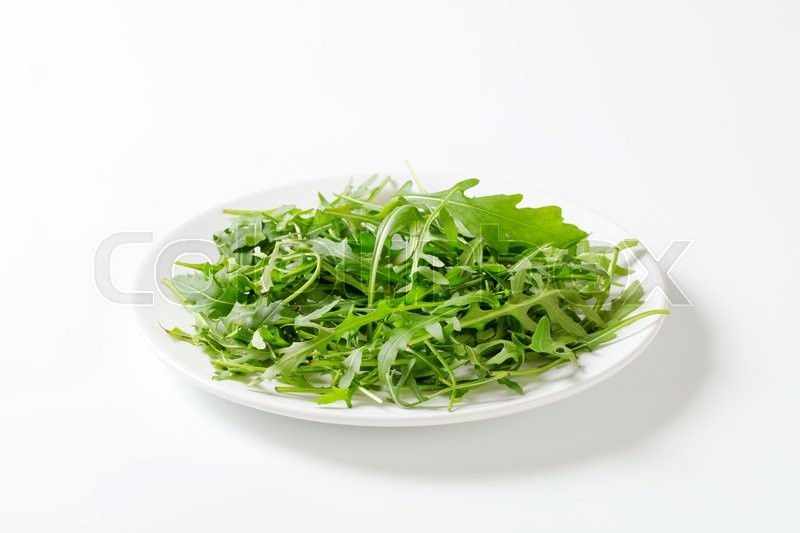 Stock image of 'Arugula leaves on a plate'
