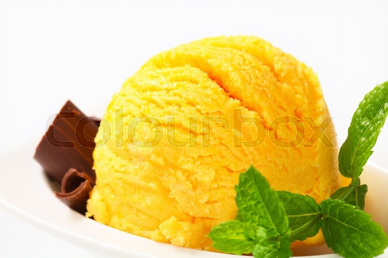 Stock image of 'Scoop of yellow ice cream garnished with chocolate curls'