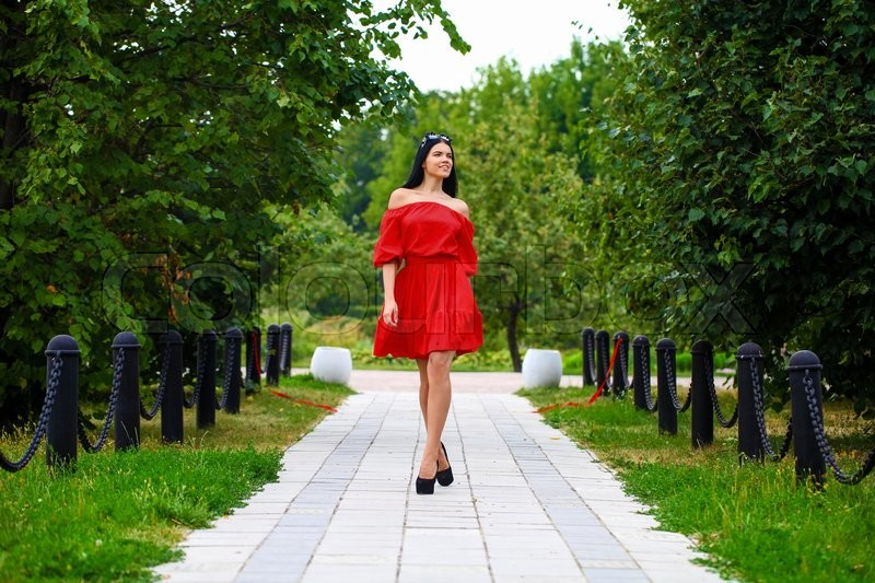 Stock image of 'Beautiful woman in red dress walking summer street'
