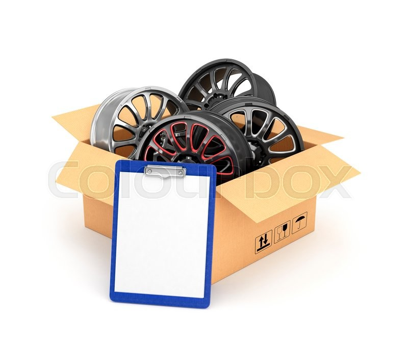 Stock image of 'Automobile rims in an open cardboard box with a folder for documents'