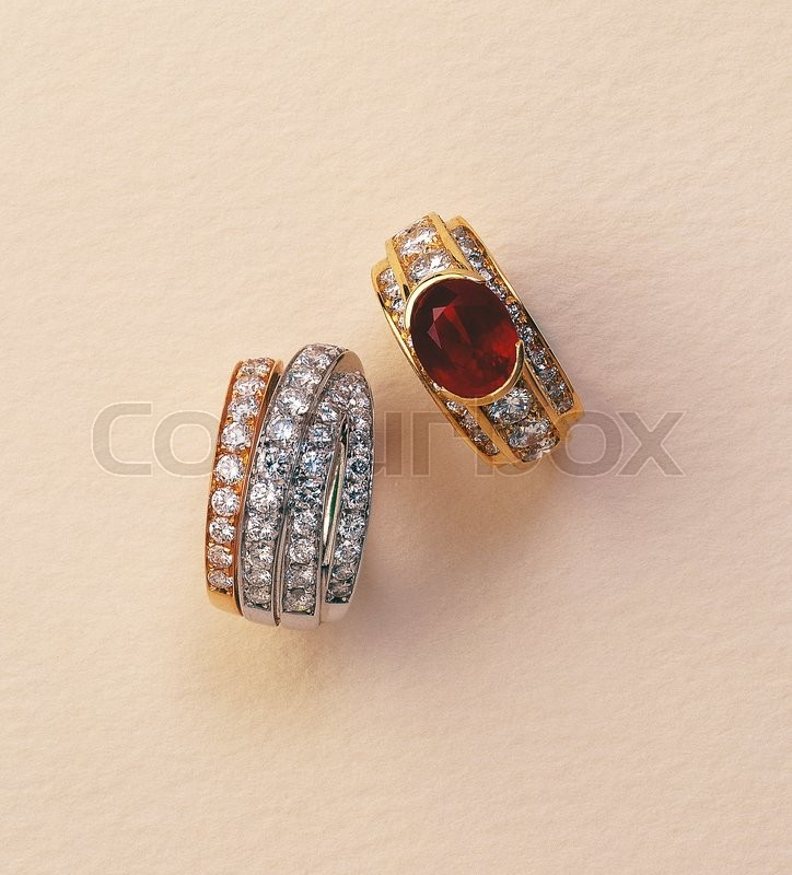 Stock image of 'Ruby and diamond ring on ocre background'