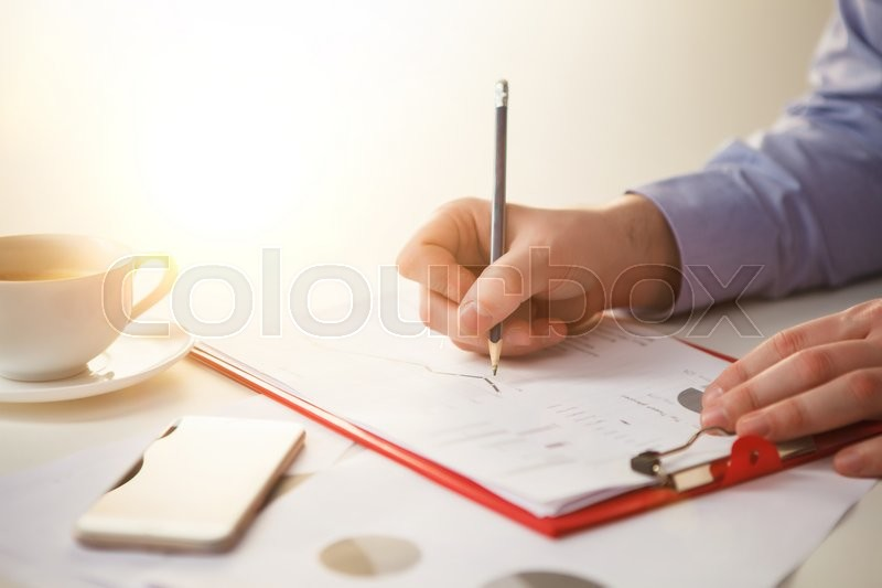 Stock image of 'The male hand drawing a graph of growth against the background of the table'