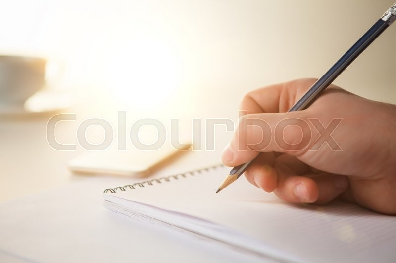Stock image of 'The male hand with a pencil and the cup of coffee and notebook on the table'