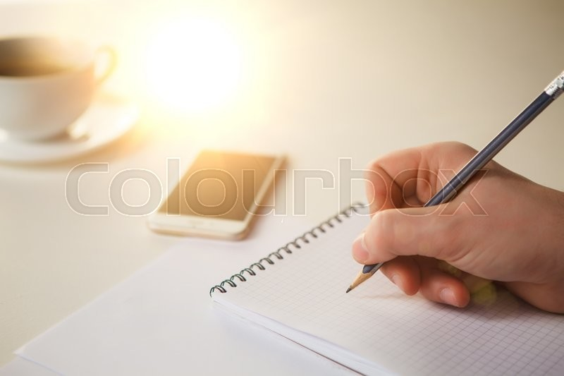 Stock image of 'The male hands with a pencil and the cup of coffee and notebook on the table'