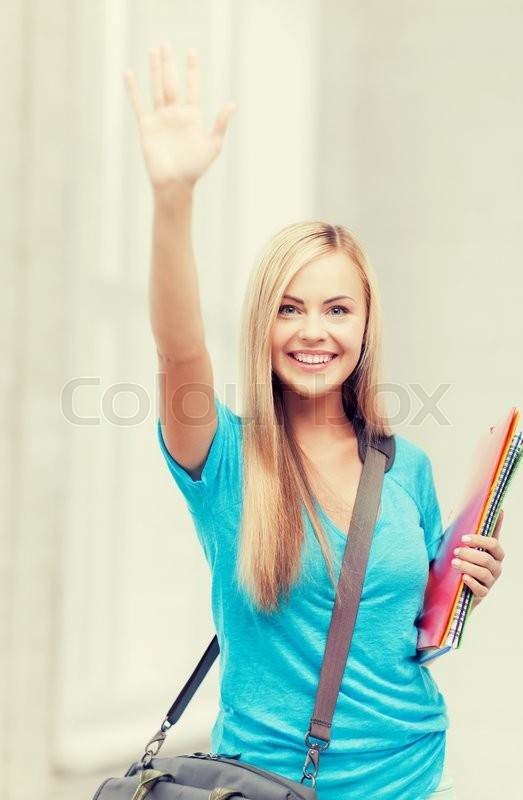 Stock image of 'picture of smiling student with folders waving her hand'