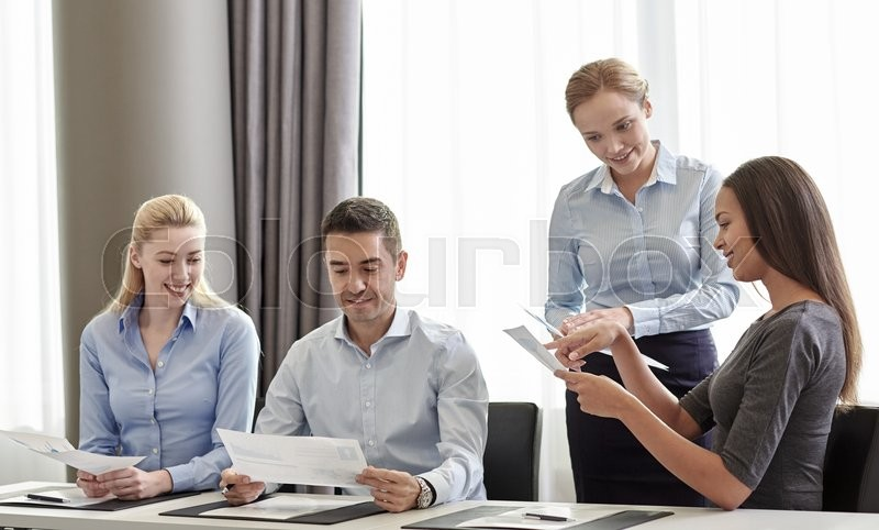 Stock image of 'business, people and teamwork concept - smiling business team with papers meeting in office'