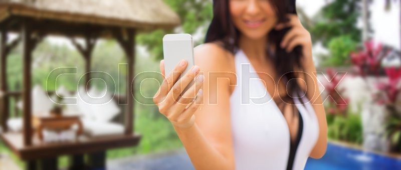 Stock image of 'summer, travel, tourism, technology and people concept - close up of sexy young woman taking selfie with smartphone over exotic hotel resort with bungalow and swimming pool background'