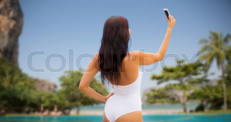 Stock image of 'summer, travel, technology and people concept - sexy young woman taking selfie with smartphone over tropical beach with palms background'