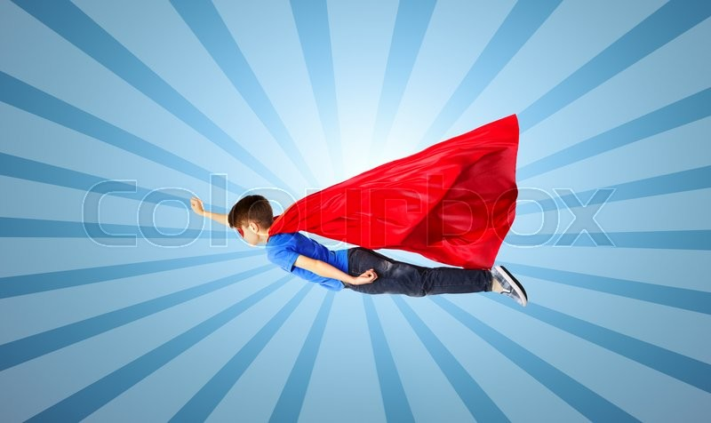 Stock image of 'happiness, freedom, childhood, movement and people concept - boy in red superhero cape and mask flying in air over blue burst rays background'