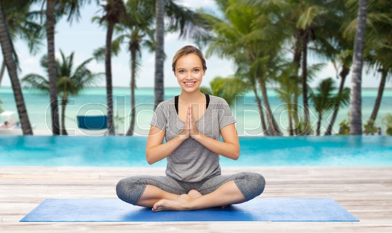 Stock image of 'fitness, sport, people and healthy lifestyle concept - woman making yoga meditation in lotus pose on mat over hotel resort pool on tropical beach background'