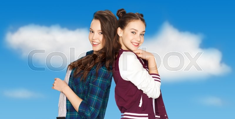 Stock image of 'people, friends, teens and friendship concept - happy smiling pretty teenage girls over blue sky and clouds background'