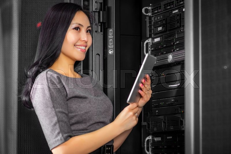 Stock image of 'Young engineer businesswoman with tablet in network server room'