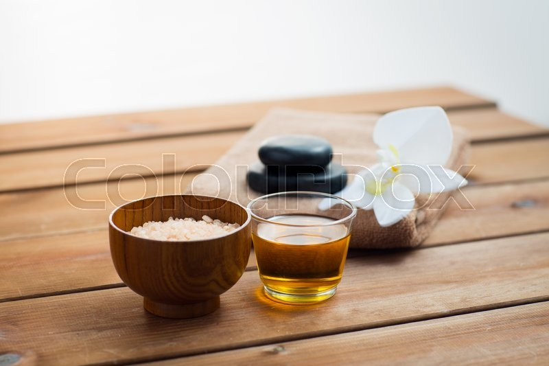 Stock image of 'beauty, spa, body care, natural cosmetics and concept - close up of pink salt with honey in glass and bath towel on wooden table'
