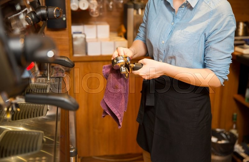 Stock image of 'equipment, coffee shop, people and technology concept - close up of woman cleaning espresso machine holder at restaurant bar'