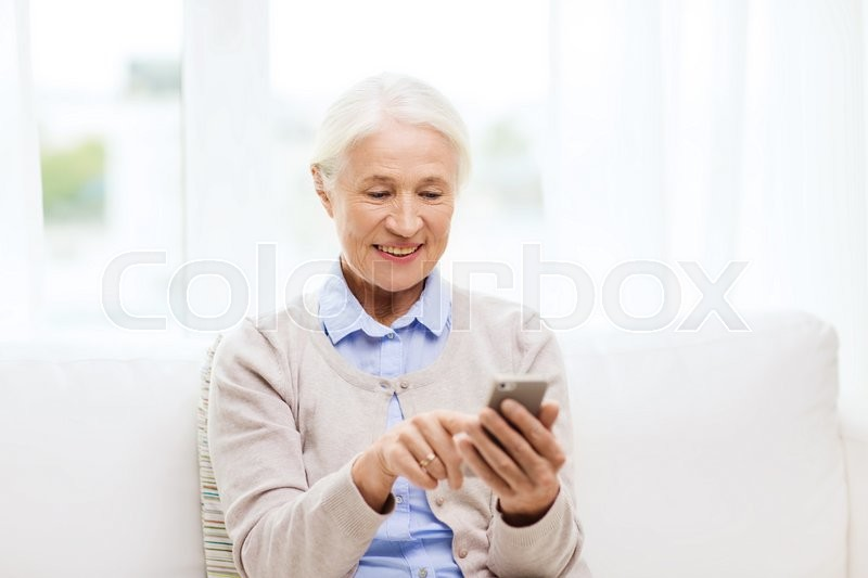 Stock image of 'technology, communication age and people concept - happy senior woman with smartphone texting message at home'