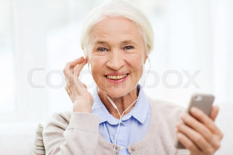 Stock image of 'technology, age and people concept - happy senior woman with smartphone and earphones listening to music at home'