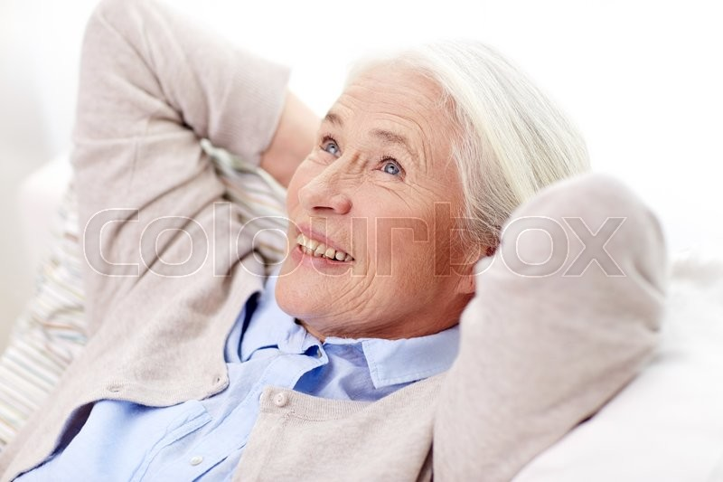Stock image of 'age, relax and people concept - happy smiling senior woman resting on sofa and dreaming at home'