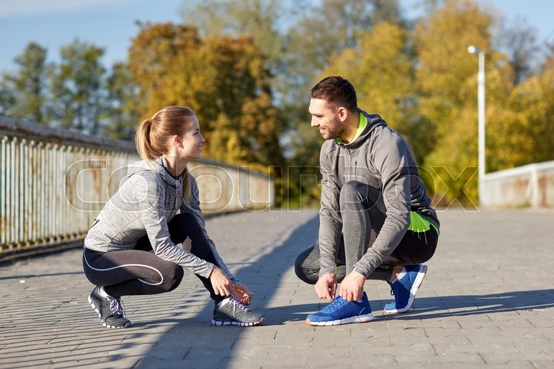 Stock image of 'fitness, sport, people and lifestyle concept - smiling couple tying shoelaces outdoors'