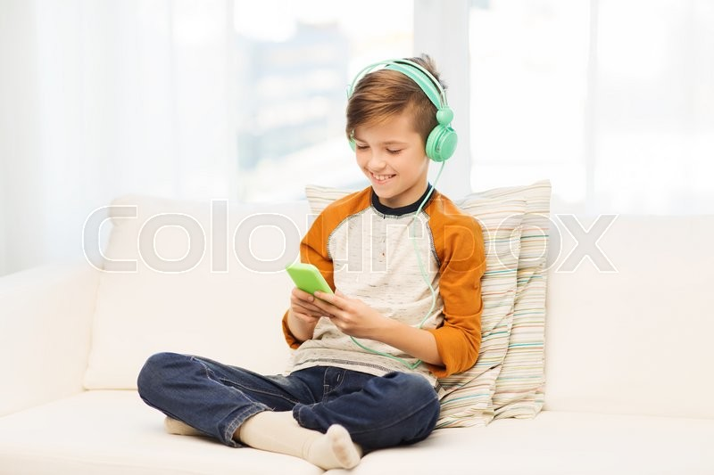 Stock image of 'leisure, children, technology and people concept - smiling boy with smartphone and headphones listening to music or playing game at home'