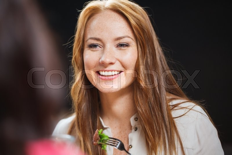 Stock image of 'leisure, food, eating, people and holidays concept - happy woman with friends having dinner at restaurant'