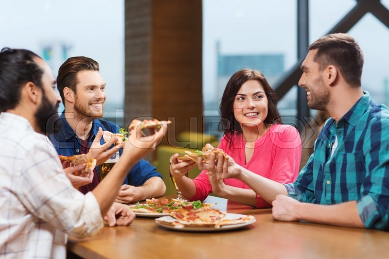 Leisure, food and drinks, people and holidays concept - smiling friends eating pizza and drinking beer at restaurant or pub, stock photo