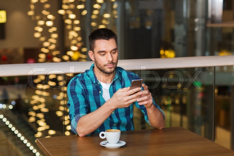 Stock image of 'leisure, technology, lifestyle and people concept - man with smartphone and coffee at restaurant'