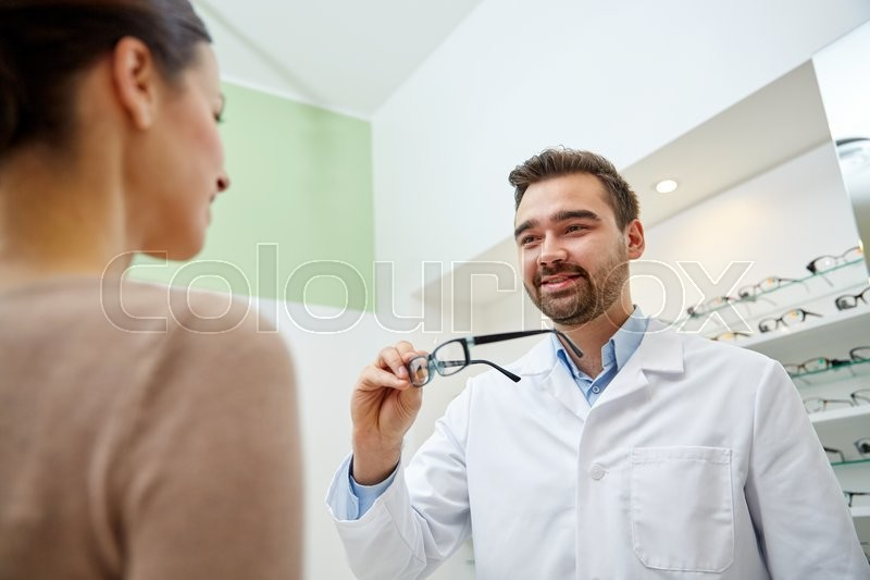 Stock image of 'health care, people, eyesight and vision concept - optician giving glasses to woman at optics store'