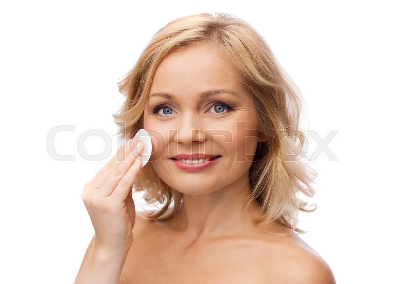 Stock image of 'beauty, people and skincare concept - young woman cleaning face and removing make up with cotton pad'