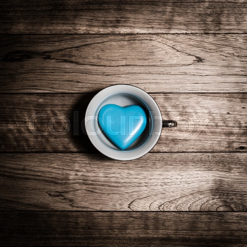 Stock image of 'Blue heart ceramic in coffee cup on old wooden plank'